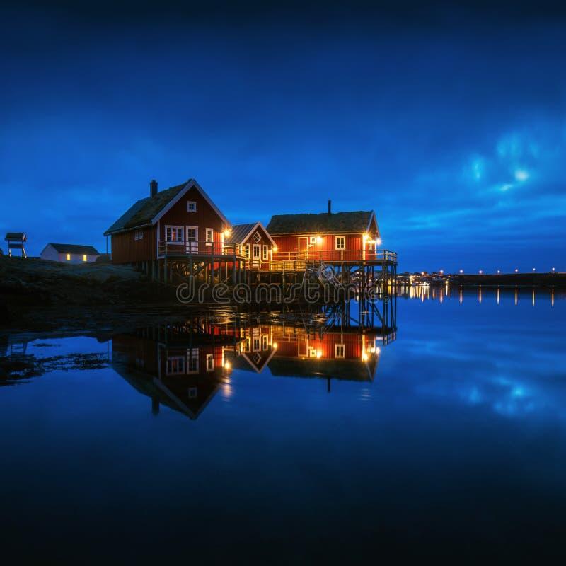 Удящ отражения Reine городка в ночи на островах Lofoten в Норвегии, над ландшафтом зимы Полярного круга со зданиями стоковые изображения