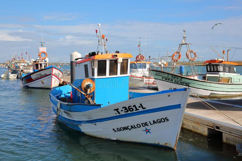 Удя гавань Санта Luzia, расположенная около Tavira, с красочными рыбацкими лодками причаливая вдоль молы стоковые изображения