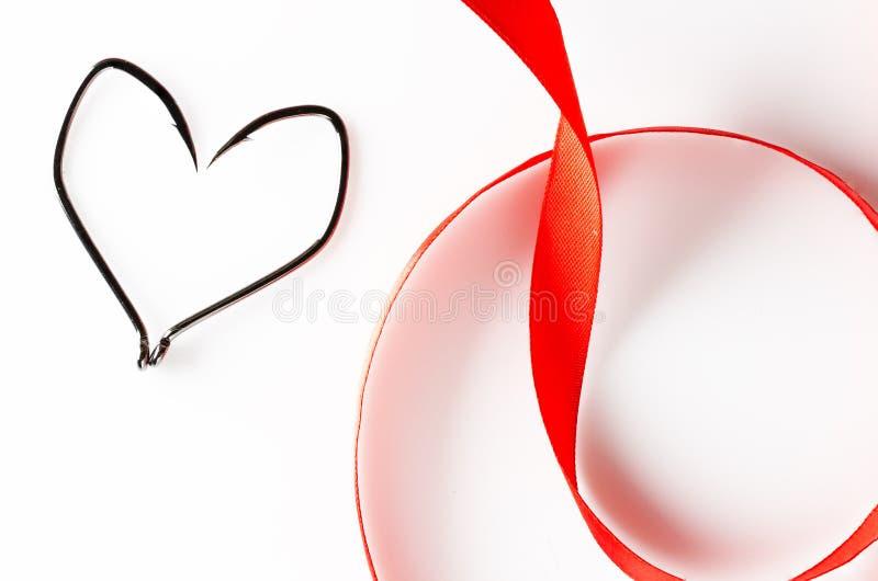 Удя крюки в форме сердца и красной ленты на белой предпосылке стоковое изображение rf