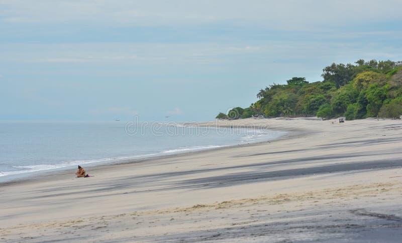 Уединенная девушка сидит на пляже на некоторое одно время, но принимает ее сотовый телефон с ей стоковое фото rf