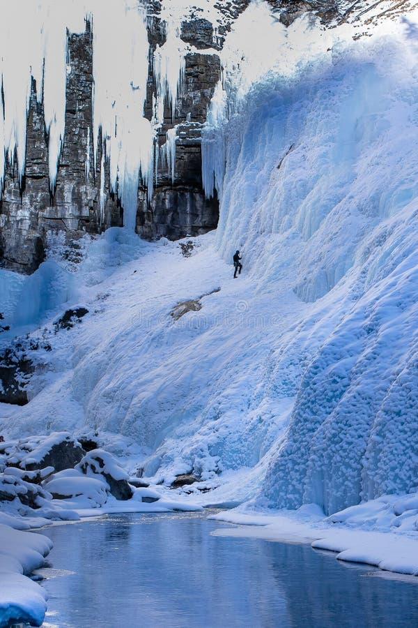 Уединенный альпинист льда масштабирует сторону замороженной горы стоковые изображения rf