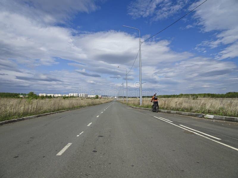 Уединенный велосипедист едет на дороге асфальта с дорожными разметками в середине полей стоковое фото rf