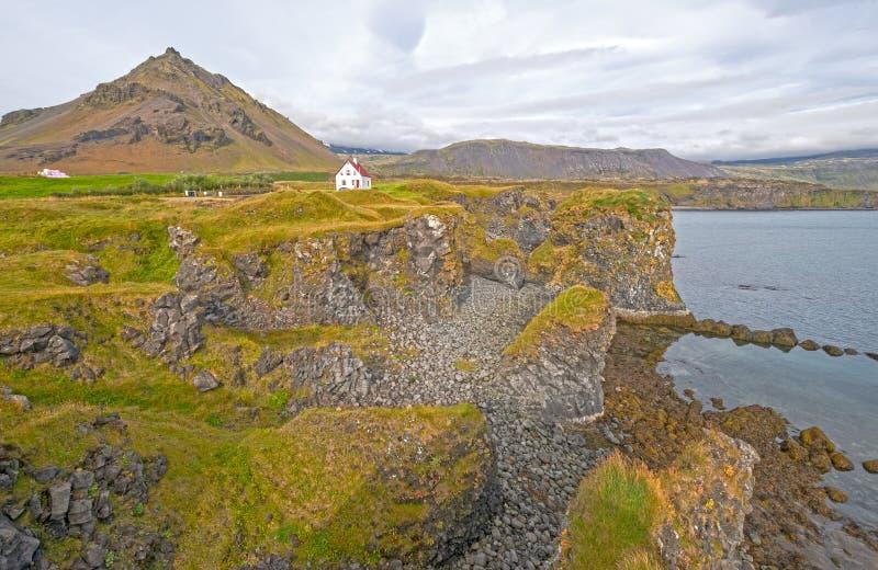 Уединенный дом на скалистом береге Исландии стоковые фотографии rf