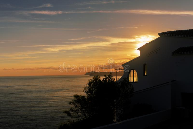 Уединенный дом с крыть черепицей черепицей крышей морем на заходе солнца Javea Spane стоковые изображения
