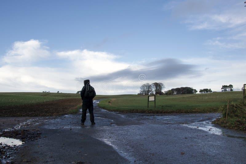 Уединенный с капюшоном hiker с положением рюкзака на перекрестки на день зим в сельской местности стоковое фото