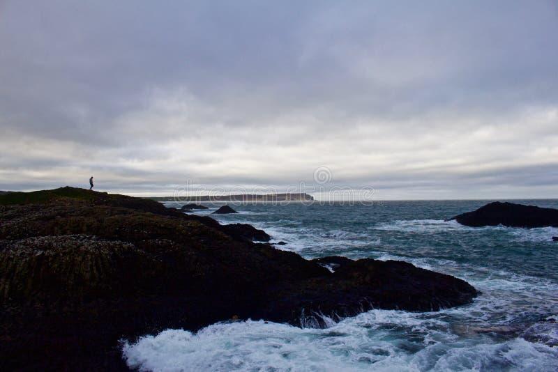 Уединенный человек обозревает океан от холма выше с турбулентными морями ниже стоковые изображения rf