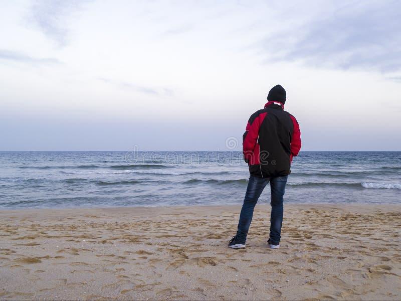 Уединенный человек стоит на пустом пляже моря и смотрит в расстояние на холодный день осени overcast стоковая фотография rf