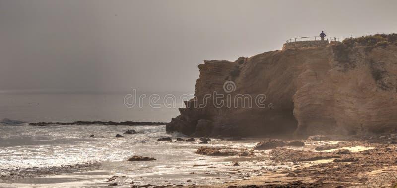 Уединённый человек стоит на перспективе как смещения тумана внутри над океаном на Cr стоковая фотография