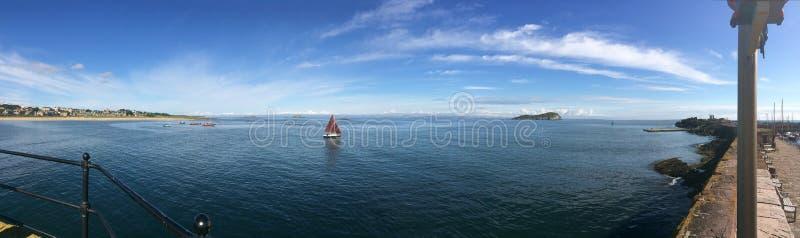 Уединённый парусник наслаждаясь морями плоского затишья голубыми в Шотландии стоковые фотографии rf