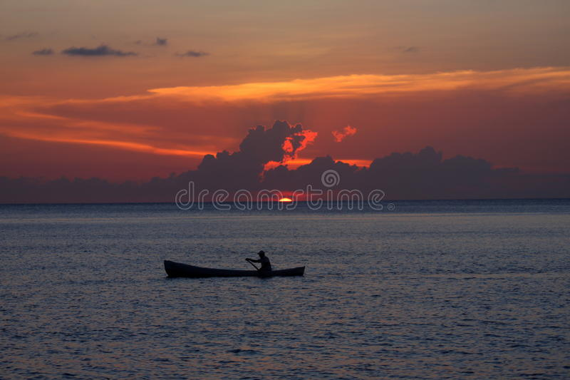 Уединённый рыболов на заходе солнца стоковые фото