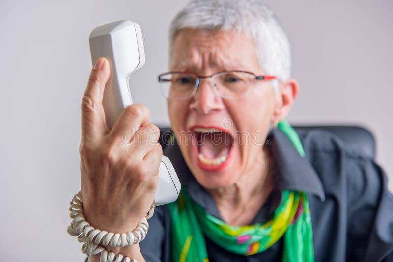Ужасное обслуживание, сердитая старшая женщина выкрикивая на телефоне стоковое изображение rf