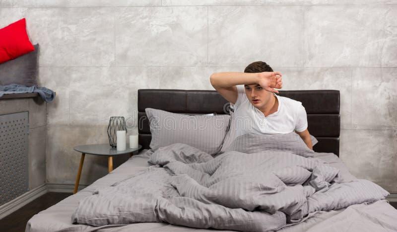 Ужаснутый молодой человек проспал вверх от кошмара и пот fr обтирать стоковое фото