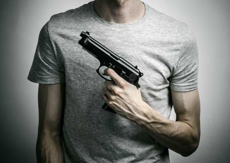 Ужас и тема огнестрельных оружий: суицид с оружием на серой предпосылке в студии стоковое изображение