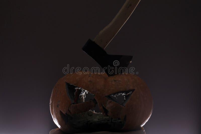 Ужас хеллоуина тыква хеллоуина убитая осью - она выглядит как ужас ось в голове поднимает фонарик домкратом o страшный и тайна стоковое фото