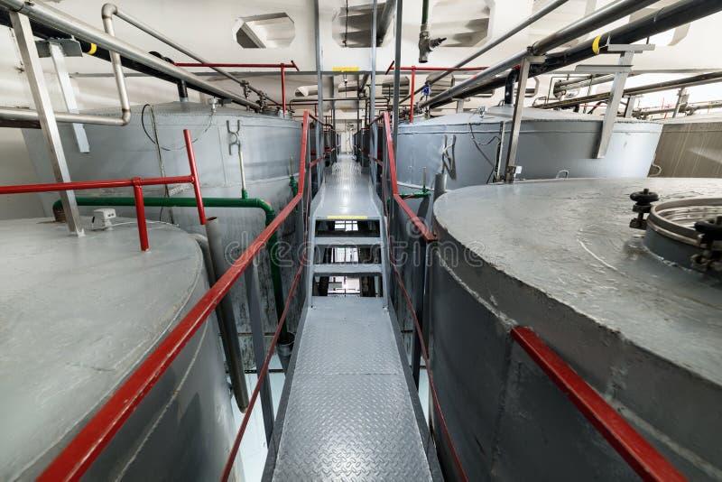 Узкая и длинная лестница между большими танками Большие стальные цилиндрические танки для заквашивать смесь дрожжей стоковое фото