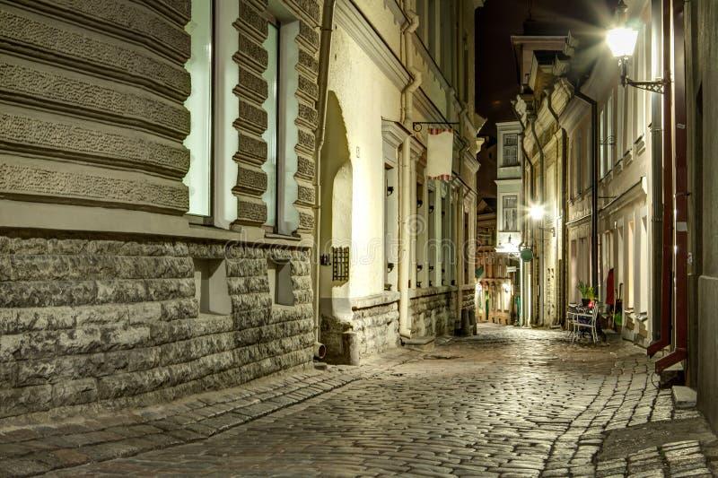 Узкая старая улица городка Таллина, Эстонии на nighttime камень стоковое фото