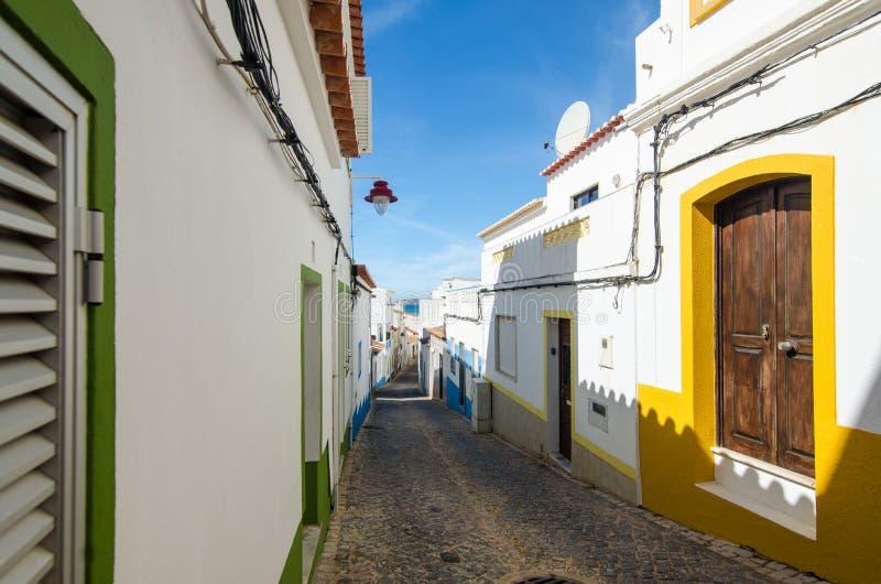 Узкая улица деревни Salema Вид на океан и побеленные дома малого рыбацкого поселка Faro, Алгарве, южная Португалия стоковая фотография