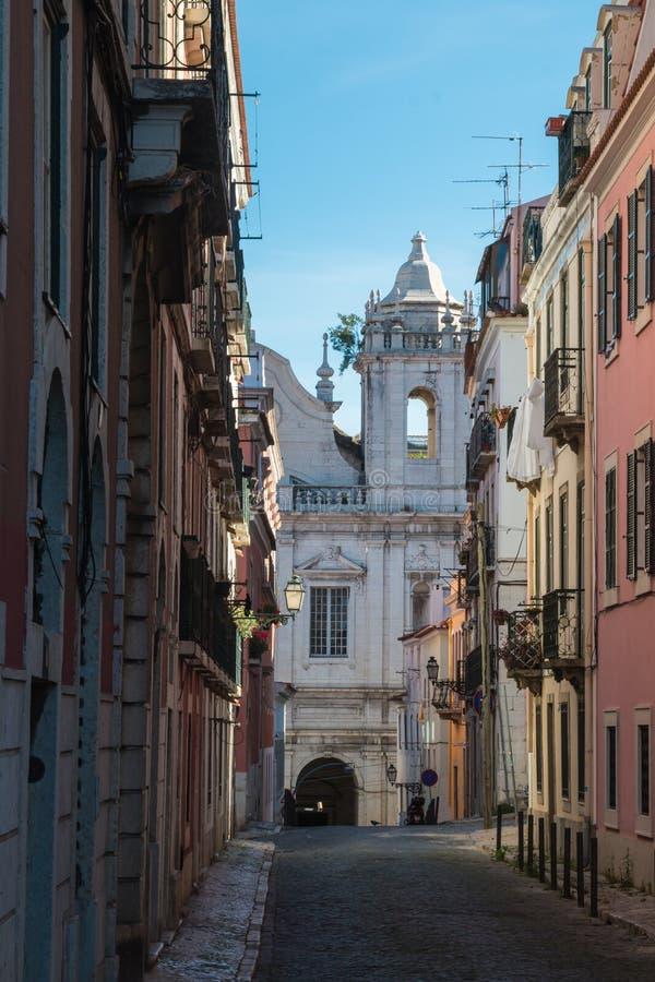 Узкая улочка и церковь, Лиссабон, Португалия стоковые фото