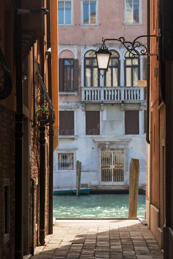 Узкая улочка со старым фонариком и взгляд к бортовому каналу в Венеции, стоковое изображение rf