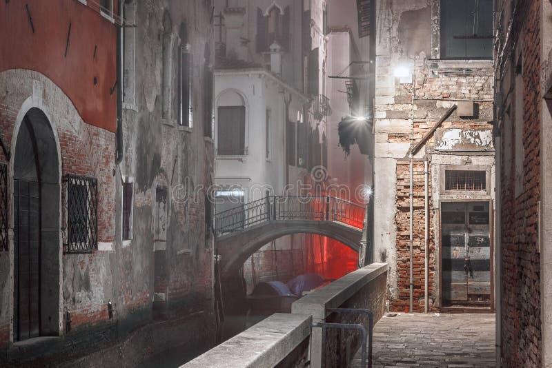 Узкая улица ночи с водяным каналом в Венеции стоковая фотография
