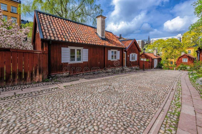 Узкая cobblestoned улица на Asoberget с типичные деревянные жилые дома покрашенные в falun красном и с белыми шторками дальше стоковая фотография rf