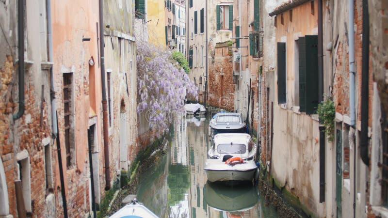 Узкие улочки Венеции - канала заполненного с водой - причаленные шлюпки стоковые изображения rf