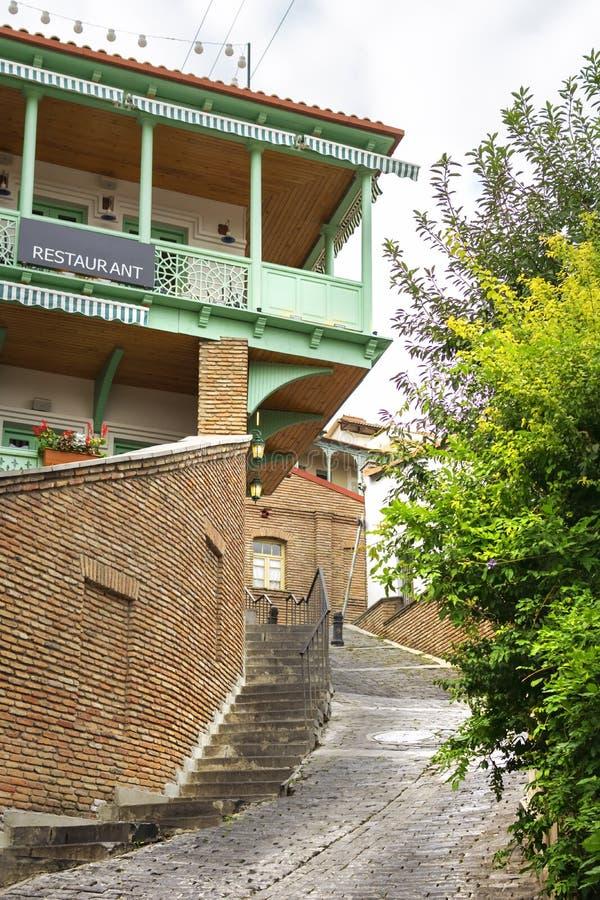 Узкие улочки городка Тбилиси старого с красивыми красочными деревянными балконами и домами красного кирпича стоковые изображения