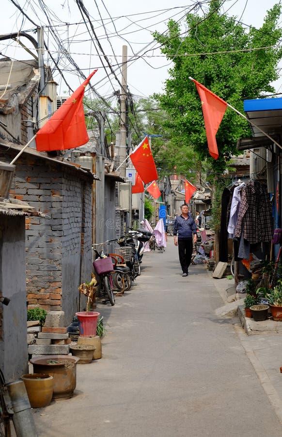 Узкий переулок традиционного hutong в Пекин, Китая с много китайских флагов во время a стоковое изображение rf