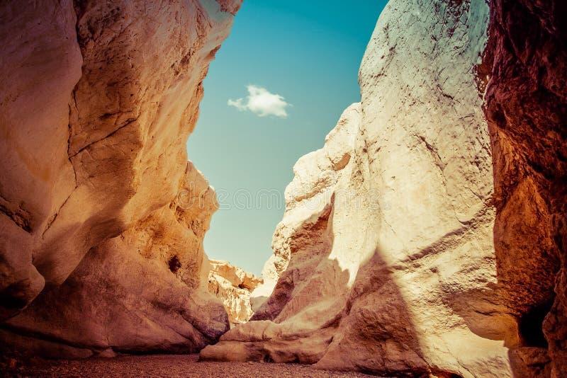 Узкий проход среди высоких утесов в каньоне Makhtesh Рэймон, отрицательное стоковое фото