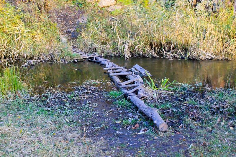 Узкий старый деревянный мост через малое реку стоковые изображения
