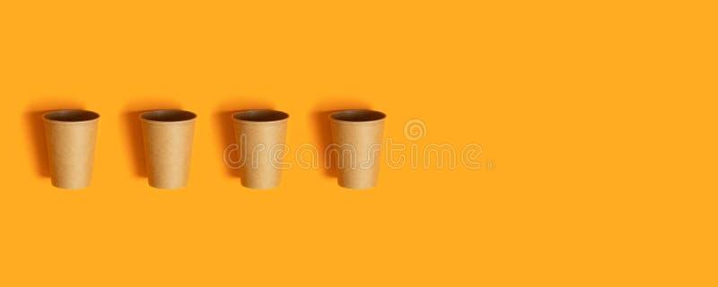 Узор с бумажными чашками на оранжевом фоне с копировальным пространстРстоковое изображение