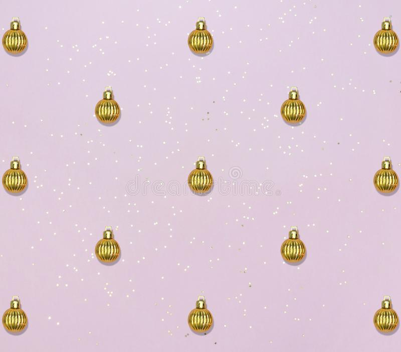 Узор с золотыми шариками и звездным конфетти на розовом пастельном фоне Рождественская или новогодняя карточка стоковые фотографии rf