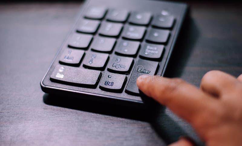 Указательный палец отжимает дальше входит кнопку черной пластмассы n стоковое фото