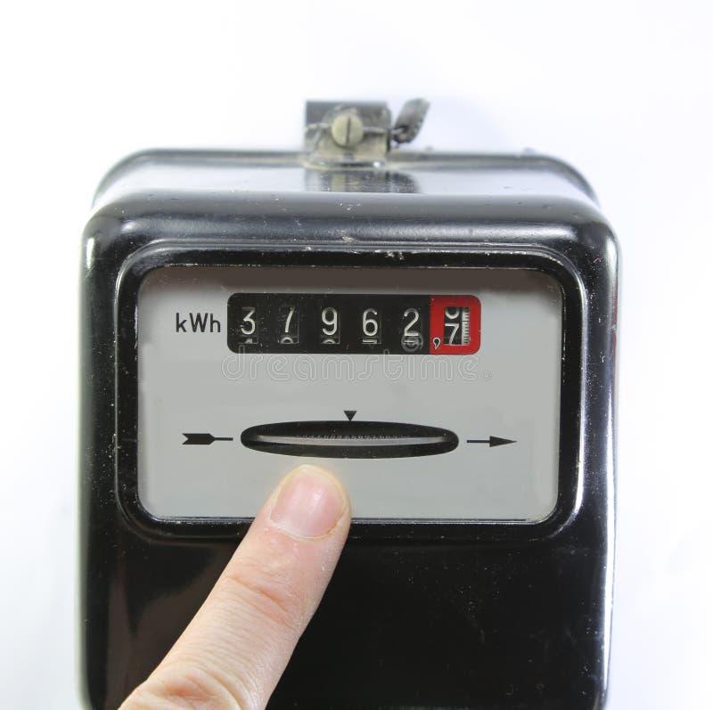 Указательный палец показывая потребление электричества на электрическом стоковое изображение