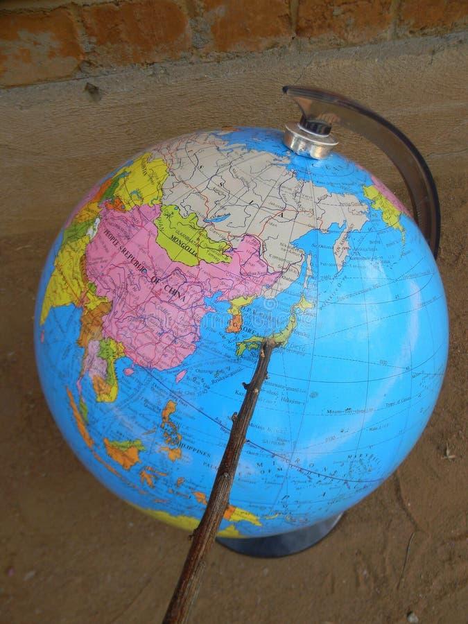Указатель показывая Японию на карте мира глобуса стоковые фото