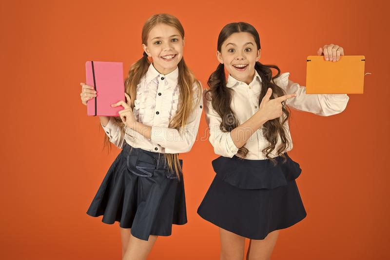 Указывать палец на обложку книги Небольшие девушки с workbooks для записи Милые школьницы держа книги урока E стоковое изображение rf