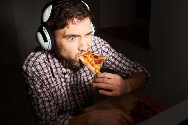 уклад жизни нездоровый Высококалорийная вредная пища, фаст-фуд Sloe вверх по портрету молодого бородатого мужского gamer с коротк стоковое изображение rf