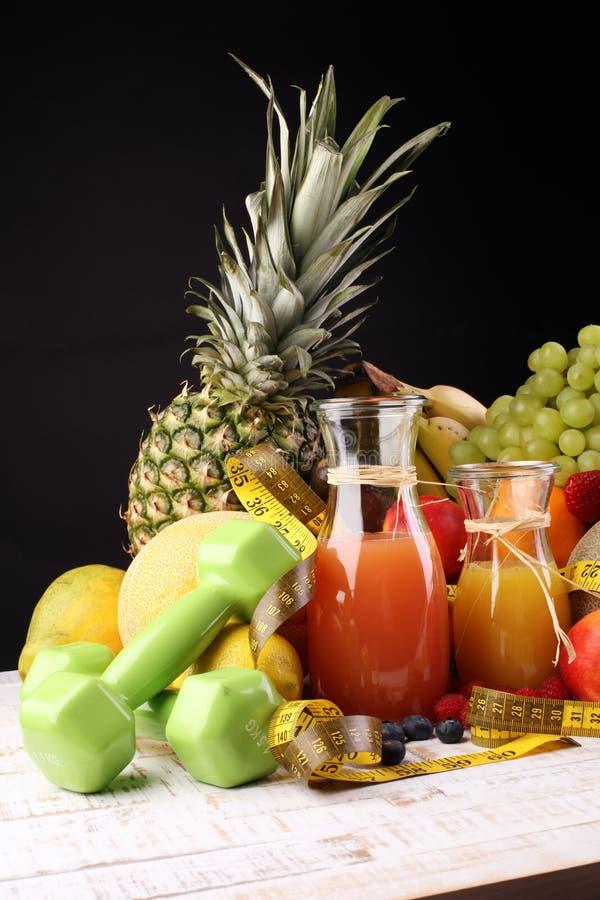 уклад жизни принципиальной схемы здоровый измеряя лента резвится оборудование фитнеса и здоровые еда и сок (фрукты и овощи, dumbe стоковое фото
