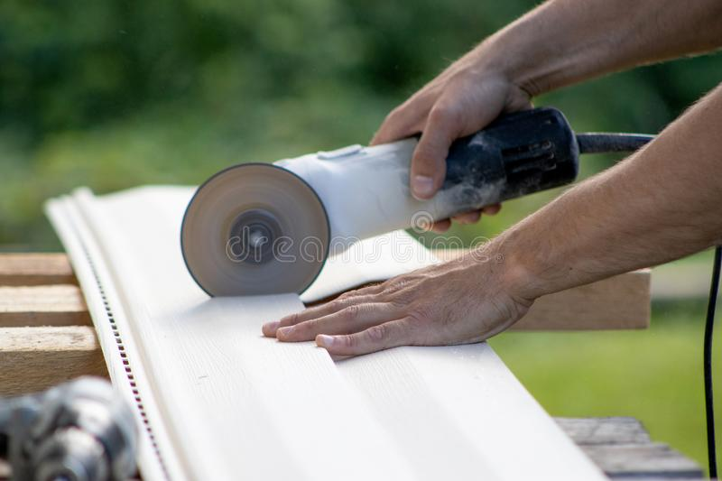 Укомплектовывает личным составом руки держа угловую машину, электрический прибор при диск, режа материал siding для строительств, стоковые изображения rf