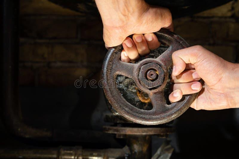 Укомплектовывает личным составом руки пробуя повернуть ржавый клапан на трубах котельной Старый боилер металла производя топление стоковые изображения rf