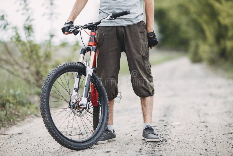 Укомплектуйте личным составом велосипедиста стоя с его велосипедом на проселочной дороге стоковая фотография