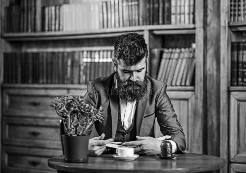 укомплектуйте личным составом возмужалое чтение Зрелый человек сидит на таблице с чашкой чаю или кофе стоковое фото rf