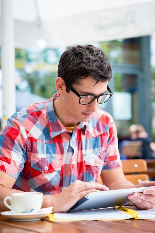 Укомплектуйте личным составом выпивая кофе в чтении кафа улицы на приборе таблетки стоковая фотография rf