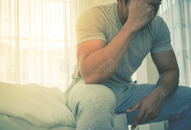 Укомплектуйте личным составом в головной боли Pyjamas на кровати от вида сверх и усильте в утре стоковые изображения