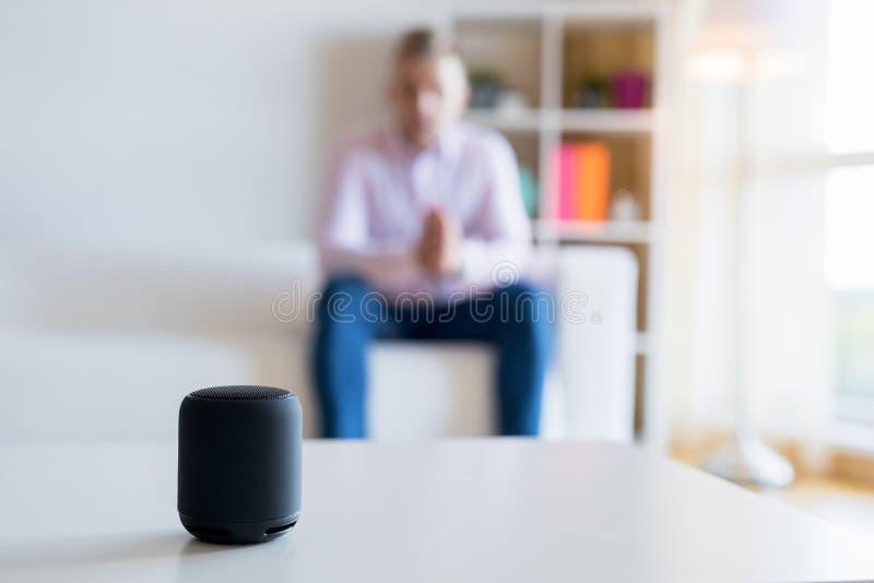 Укомплектуйте личным составом говорить к виртуальному ассистентскому умному диктору в живущей комнате стоковые фото