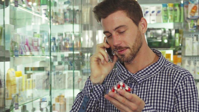 Укомплектуйте личным составом говорить на телефоне о пилюльках в аптеке стоковая фотография rf
