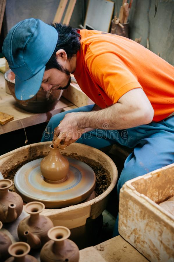 Укомплектуйте личным составом делать искусство гончарни, конец работы глины вверх по съемке рук стоковые изображения