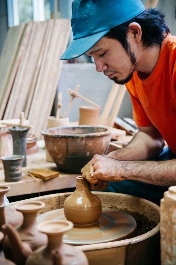 Укомплектуйте личным составом делать искусство гончарни, конец работы глины вверх по съемке рук стоковые фотографии rf