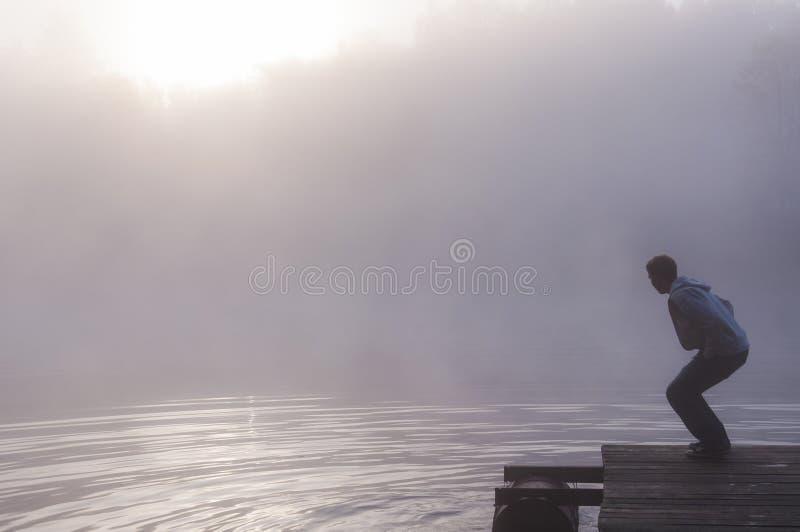 Укомплектуйте личным составом делать пульсации воды на пристани озера на туманном восходе солнца стоковые изображения rf