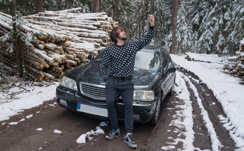 Укомплектуйте личным составом делать selfie на телефоне около автомобиля в лесе зимы стоковые фото